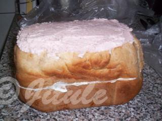 Vršek dortu odkrojíme, aby byl rovný a namažeme turistickou pomazánkou.
